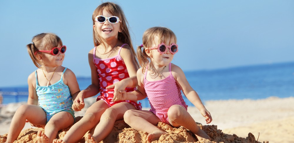 Three girls with sunglasses on beach